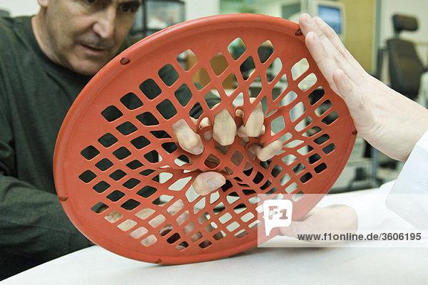 Patientin mit Handübungsband zur ergotherapeutischen Behandlung