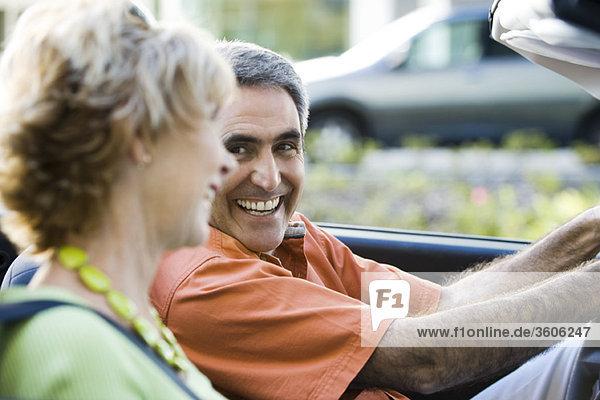 Ein reifes Paar  das zusammen fahren will  ein Mann  der seine Frau anlächelt.