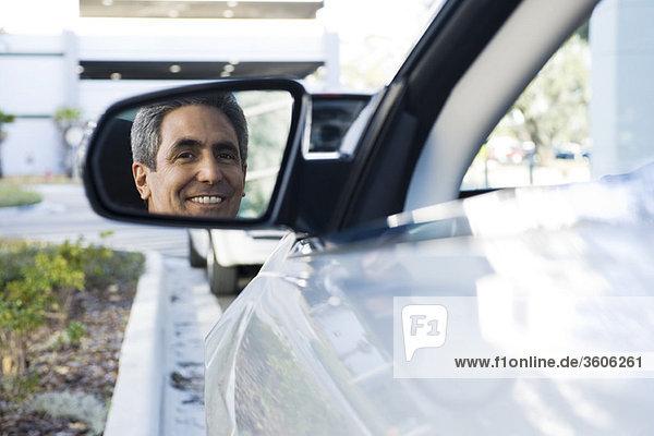 Mann sitzt im geparkten Auto  Spiegelung im Seitenspiegel