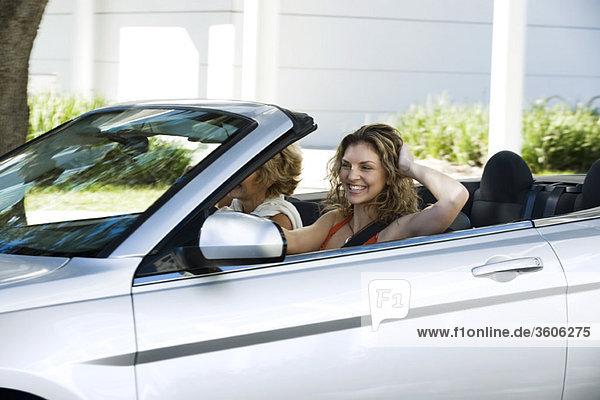 Junge Frau mit Freund beim Cabriofahren