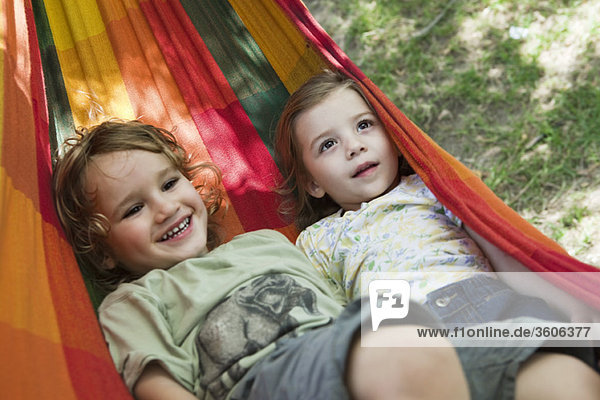 Young brother and sister lying in hammock together