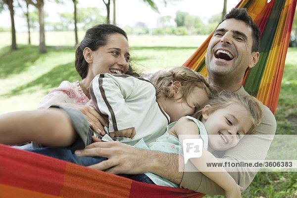 Familie lacht zusammen auf der Hängematte