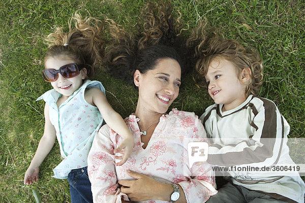 Mutter auf Gras liegend mit kleinen Kindern