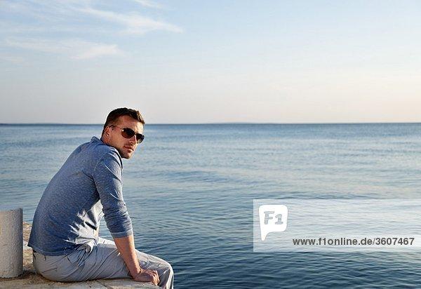 Mann am Meer sitzend