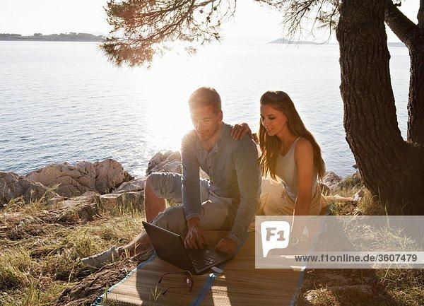 Paar mit kabellosem Laptop auf dem Seeweg