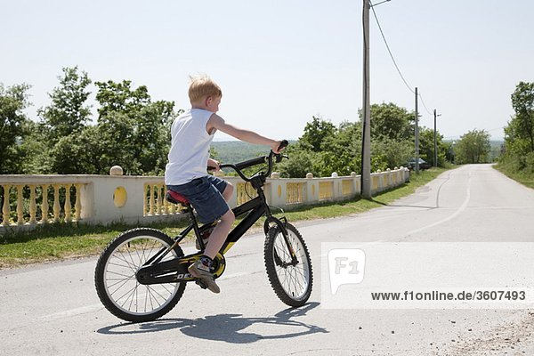 Junge auf dem Fahrrad auf der Landstraße