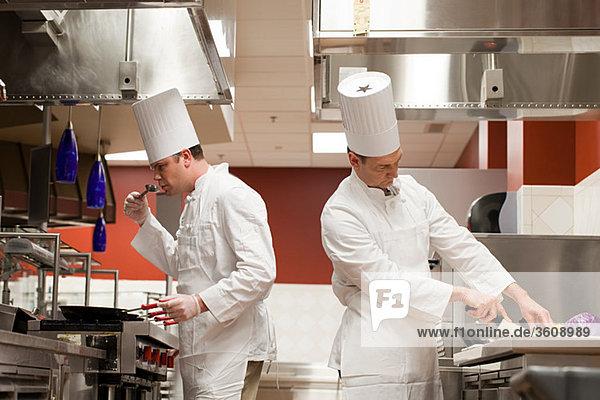 Küchenchefs bei der Zubereitung von Speisen in der Großküche