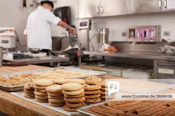 Männlicher Koch backt Kekse in der Großküche
