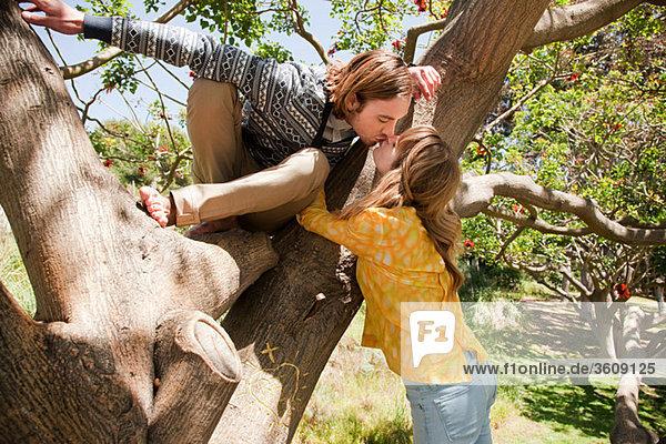 Mann im Baum  der sich dazu neigt  seine Freundin zu küssen.