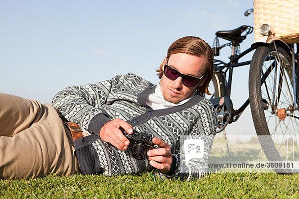 Junger Mann im Feld mit Kamera und Fahrrad