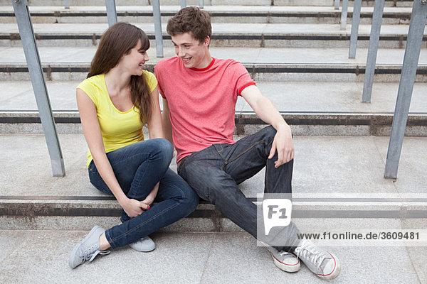 Junges Paar auf einer Treppe sitzend