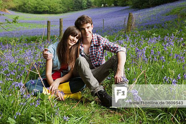 Junges Paar in einem Feld von Hasenglöckchen