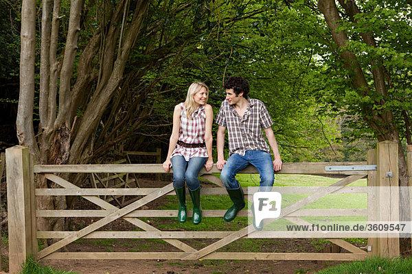 Junges Paar auf dem Tor sitzend
