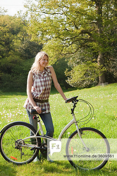 Young woman in field with bicycle