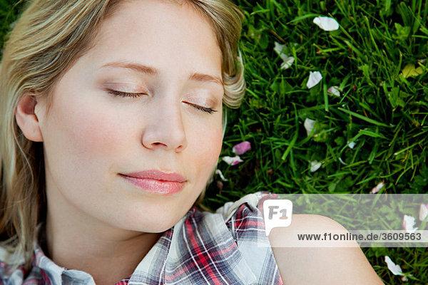 Junge Frau auf Gras liegend mit geschlossenen Augen