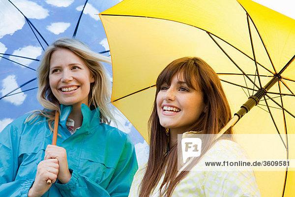 Zwei junge Frauen mit Regenschirmen