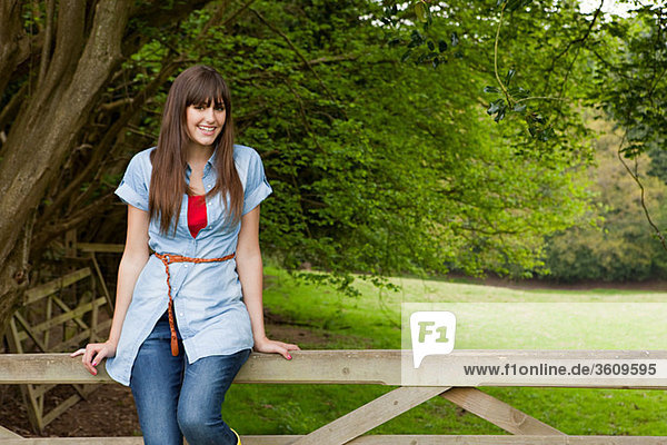 Young woman sitting on gate