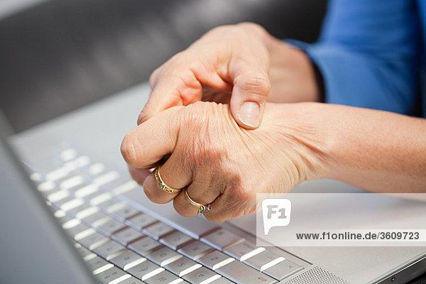 Laptop und Frau mit Schmerzen in der Hand