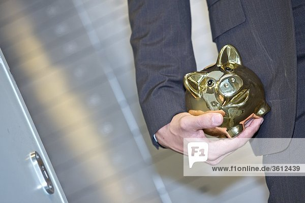 Mann vor Bankschließfächern mit goldenem Sparschwein  close-up