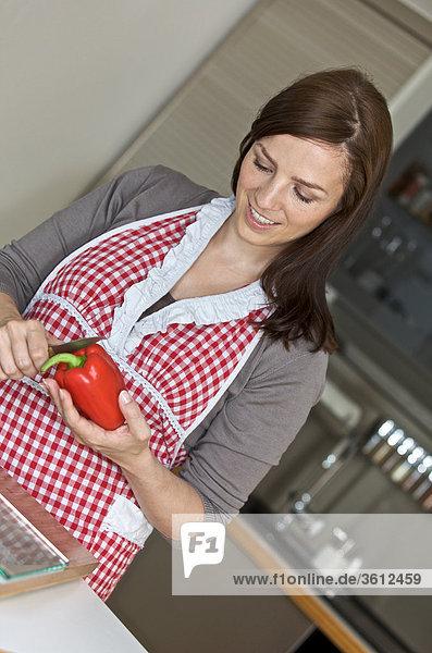 Frau schneidet eine Paprika in der Küche Frau schneidet eine Paprika in der Küche