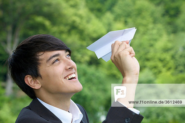 Geschäftsmann hält Papierflugzeug  Profil