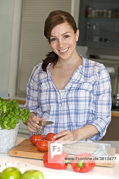 Frau schneidet Tomaten in der Küche