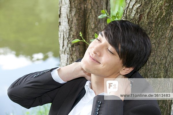 Junger Geschäftsmann lehnt an einem Baumstamm