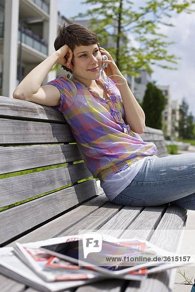 Junge Frau mit Handy  iPad  Zeitungen und Zeitschrift auf einer Bank