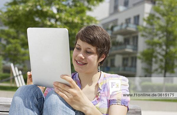 Junge Frau benutzt einen iPad auf einer Bank