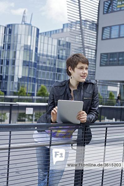 Junge Frau benutzt einen iPad vor einem Bürogebäude