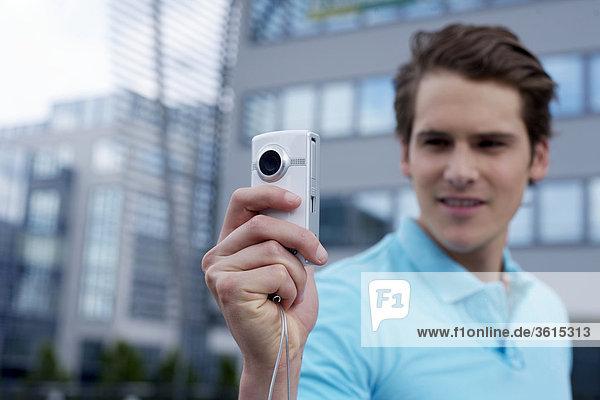 Junger Mann mit Smartphone vor einem Bürogebäude