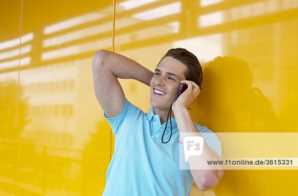 Junger Mann telefoniert mit Handy
