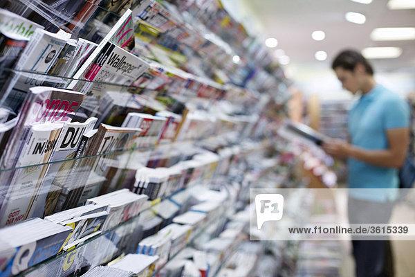 Junger Mann liest eine Zeitschrift in einem Laden