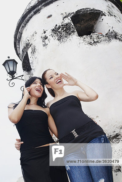 Low angle view of two young women shouting