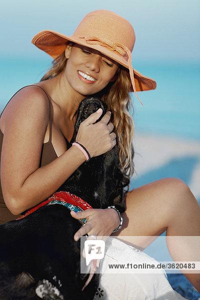 Nahaufnahme einer jungen Frau mit einem Hund am Strand sitzen
