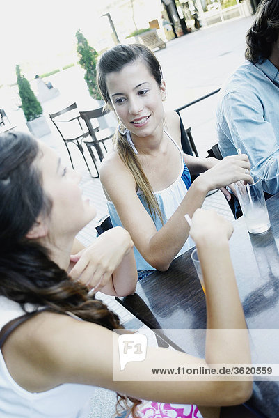 Two young women and a man sitting together in a sidewalk cafe