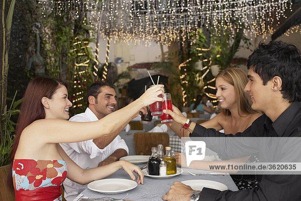 Seitenansicht vier Personen an einem Tisch sitzen und Rösten mit Brille