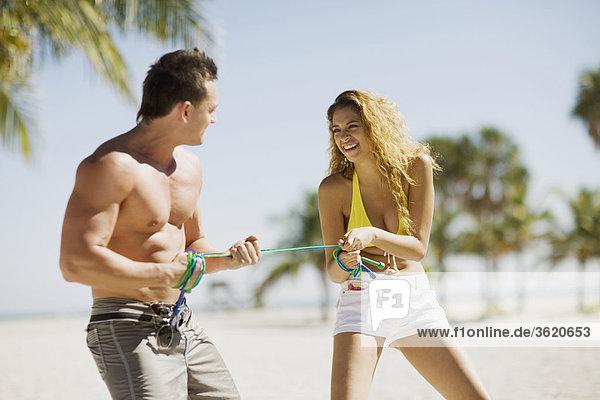 junges Paar stehen am Strand und Seilzug