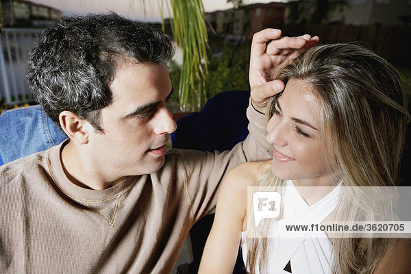 Close-up of a mid adult man touching a mid adult woman's forehead
