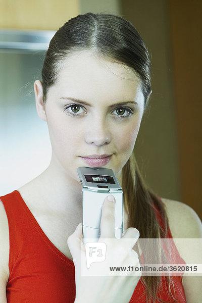 Portrait of a junge Frau hält ein Mobiltelefon