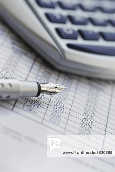 Nahaufnahme von einem Füllfederhalter mit einem Taschenrechner auf Finanzbericht
