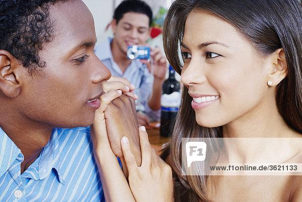 Nahaufnahme eines jungen Paares Blick auf einander mit einem jungen Mann  der Aufnahme eines Bildes