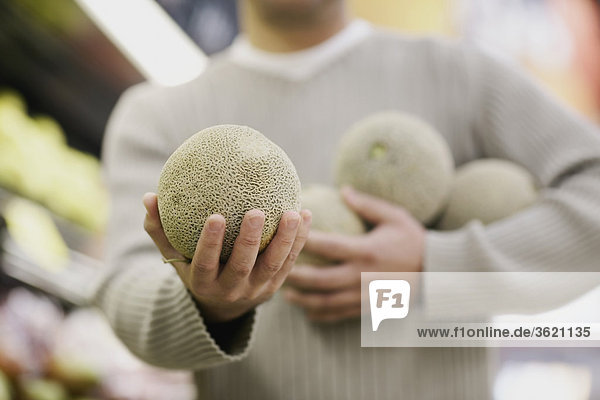 Close-up of a man's hand holding a melon