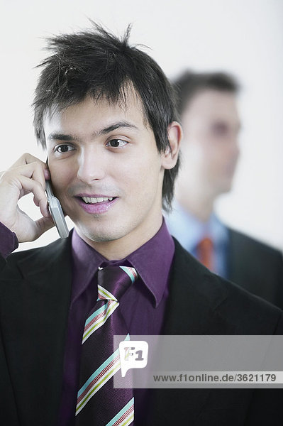 Close-up of a businessman using a mobile phone with another businessman behind him