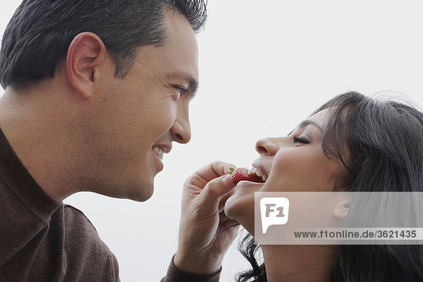 Close-up of a mid adult man feeding a strawberry to a young woman