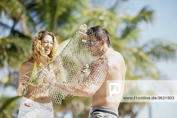 Frau setzen ein Fischernetz über einen jungen Mann und lächelnd