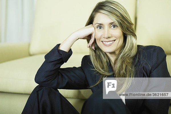 Portrait of a businesswoman sitting in front of a couch and smiling