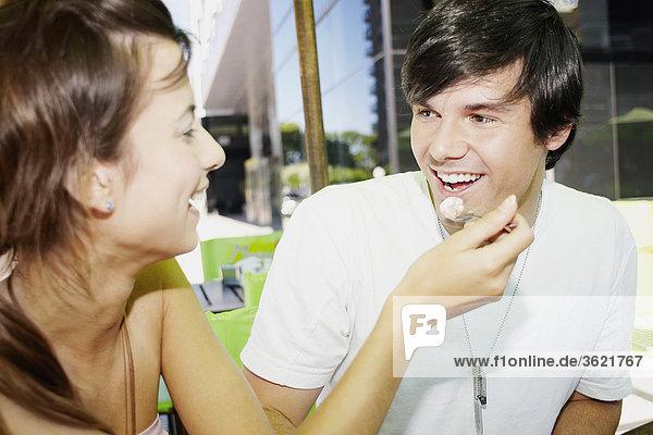 Nahaufnahme einer jungen Frau Fütterung Eis  ein junger Mann