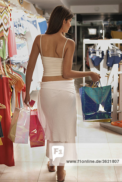 Rear view of a woman walking with shopping bags