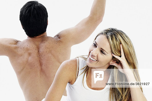 Nahaufnahme einer Mitte erwachsen Frau lächelnd mit einem mittleren erwachsenen Mann hinter ihr